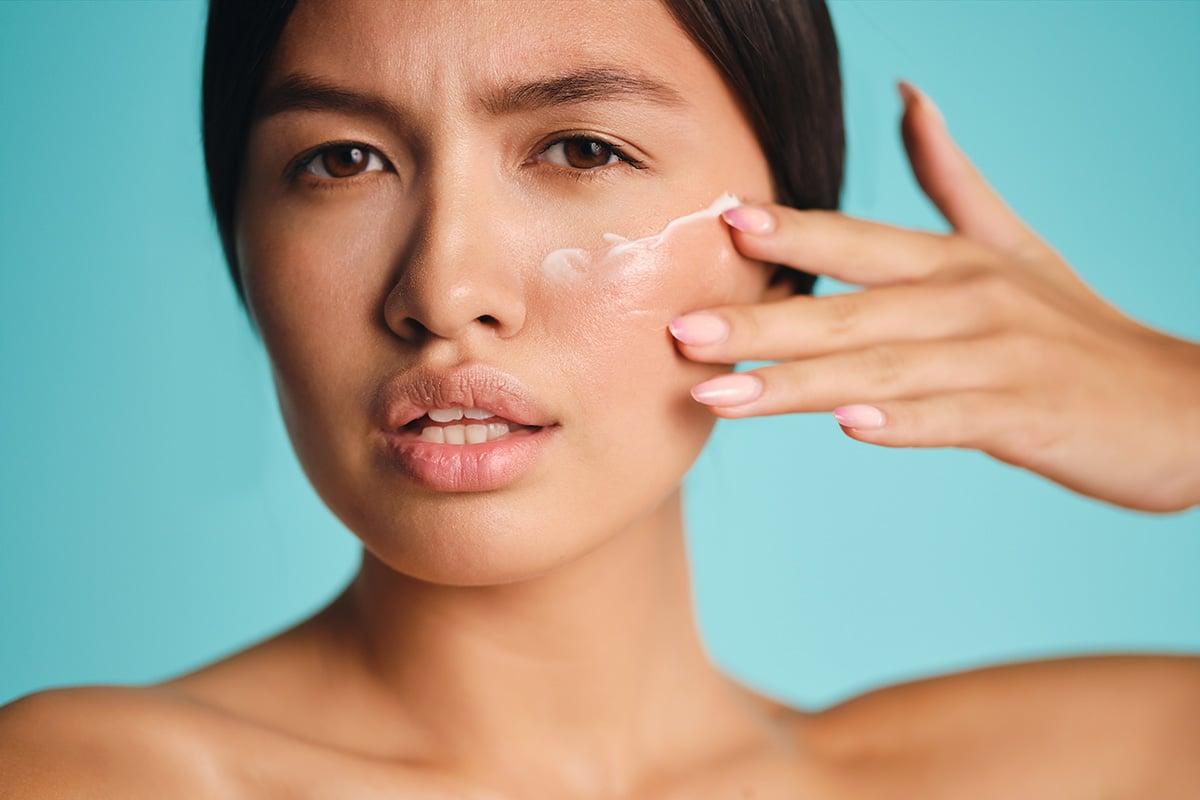 donna che stende crema sul viso
