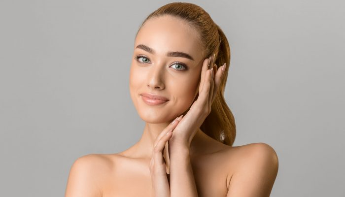 Skin care concept. Beautiful woman touching face with perfect fresh skin, grey background